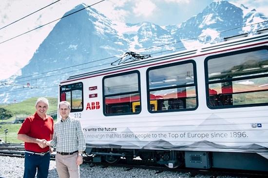 少女峰铁路首席执行官Urs Kessler和ABB瑞士总裁Remo Lutolf站在ABB全新品牌涂装的列车前