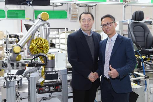 北汽李尔总经理宋晓辉先生(左)与优傲机器人公司华北大区经理倪荣刚先生(右)参观优傲UR限量版黄金机器人在北汽李尔生产线的部署
